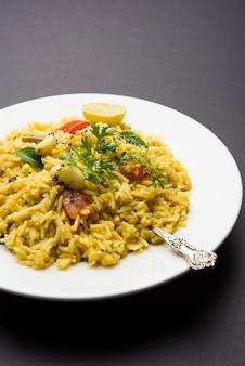 Даль кичади или кхичди вкусный индийский рецепт, который подается в миске на мрачном фоне, состоит из товар дал и риса в сочетании с цельными специями, луком, чесноком, помидорами и т. д. выборочный фокус
