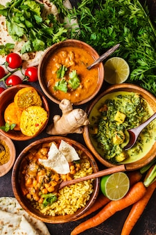 Dal, palak paneer, curry, rice, chapati, chutney in wooden bowls on dark table.