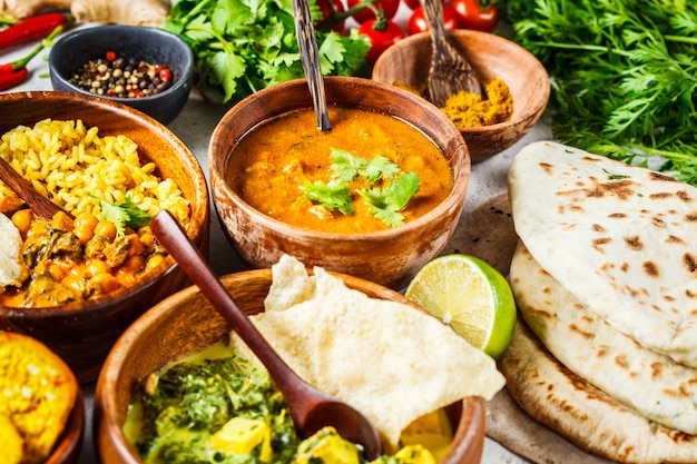 Dal, palak paneer, curry, rice, chapati, chutney in wooden bowls on white table.