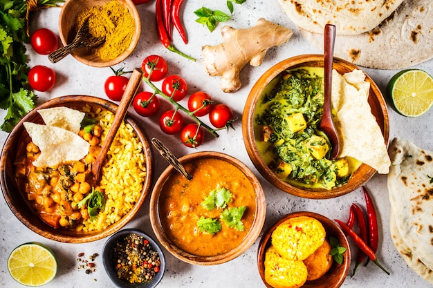 Dal、palakパニール、カレー、ライス、チャパティ、白いテーブルの上の木製ボウルのチャツネ。