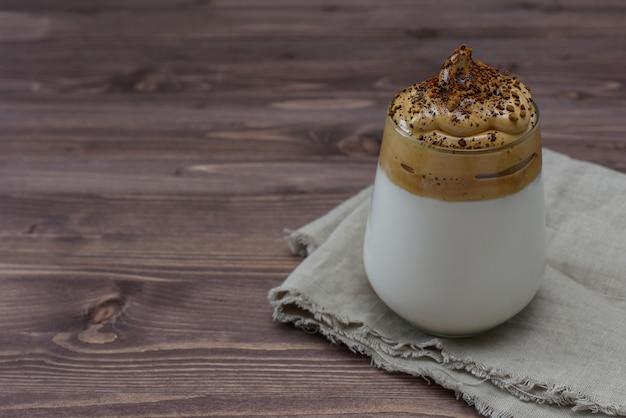 Dalgona coffee, модный пушистый сливочный взбитый кофе на деревянном фоне с копией пространства. деревенский стиль домодельный кофе dalgona в стекле с молоком.