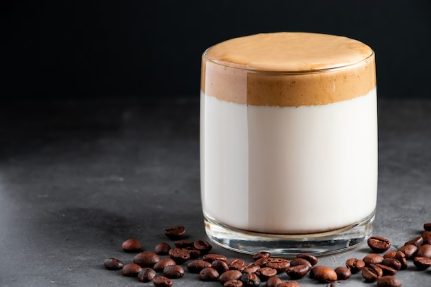 Dalgona coffee on a dark background glass of trendy korean ice drink made from milk and fluffy foam