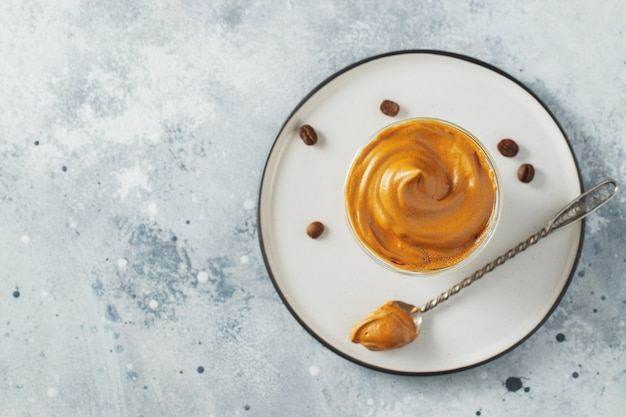 ダルゴナコーヒー。コーヒーの泡とミルクが入った、アイスのふわふわのクリーミーなホイップトレンドドリンク。 covid-19市の封鎖と自己検疫中の流行の飲み物、外出禁止令。コピースペースのある上面図。