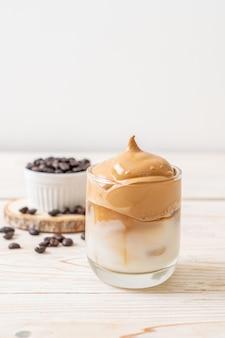 Кофе далгона. ледяной пушистый сливочно-взбитый трендовый напиток с кофейной пеной и молоком. модный напиток во время блокировки города covid-19 и самостоятельного карантина, концепция оставайся дома.