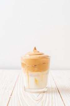 Кофе далгона. ледяной пушистый сливочно-взбитый трендовый напиток с кофейной пенкой и молоком. модный напиток во время блокировки города covid-19 и самостоятельного карантина, концепция оставайся дома.