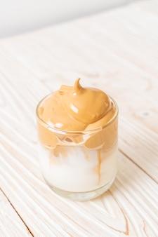 Кофе далгона. пышный сливочно-взбитый трендовый напиток со льдом с кофейной пенкой и молоком