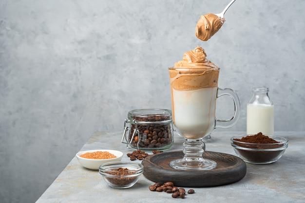 透明なグラスに入ったダルゴナ コーヒーと、灰色の壁に泡の入ったスプーン。水平ビュー、コピー スペース。