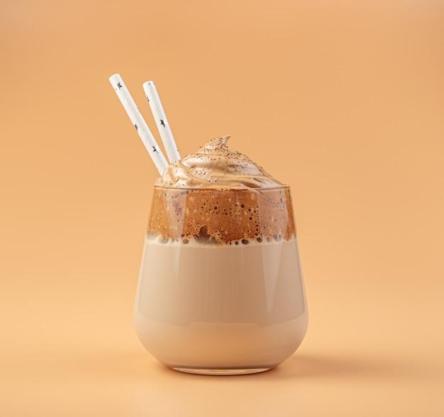 Кофе dalgona в прозрачном стакане с соломкой на оранжевой стене. вид сбоку, крупный план.