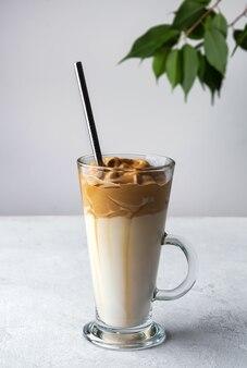 Кофе dalgona в высоком стакане с соломой на белом пространстве
