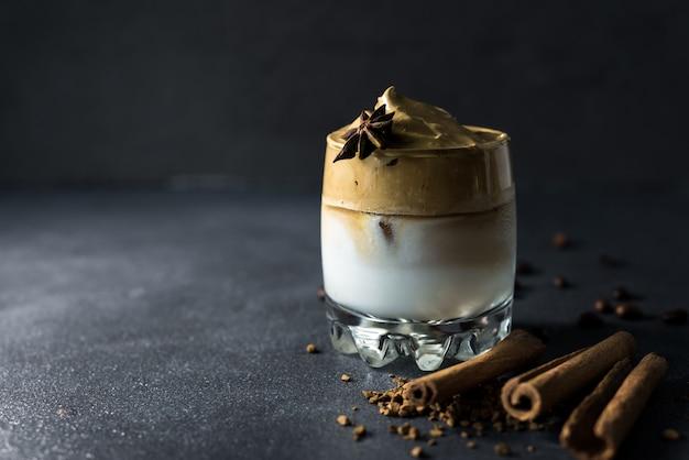 어두운 배경에 투명 컵에 dalgona 커피. 인스턴트 커피, 설탕 및 우유와 함께 한국 음료.