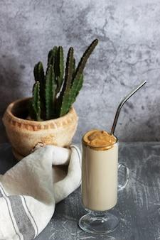 カクテルストローとサボテンがコンクリートのテーブルの上にある透明なカップのダルゴナコーヒー。