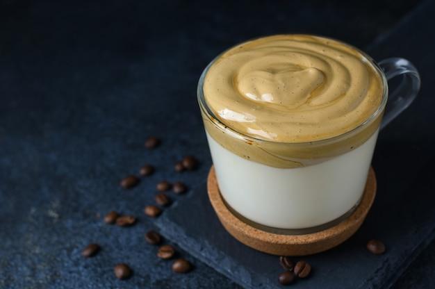 어두운 돌 배경에 원두 커피와 유리 컵에 dalgona 커피. 공간을 복사하십시오. 설탕, 인스턴트 커피 및 온수를 사용한 수제 dalgona 폼.