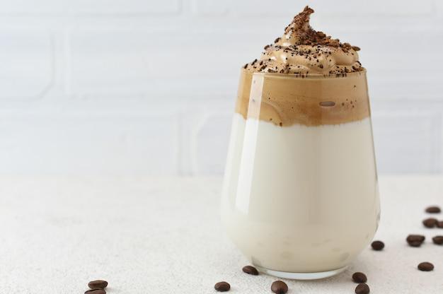 유리에 달고나 커피는 커피 콩으로 장식. dalgona 커피, 복사 공간 흰색 배경에 솜 털 휘 핑된 커피.