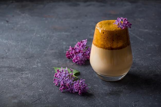 어두운 배경에 라일락 꽃과 키 큰 유리에 dalgona 커피. 설탕과 물로 채운 인스턴트 커피는 차가운 우유에 첨가됩니다. 시원한 여름 음료.