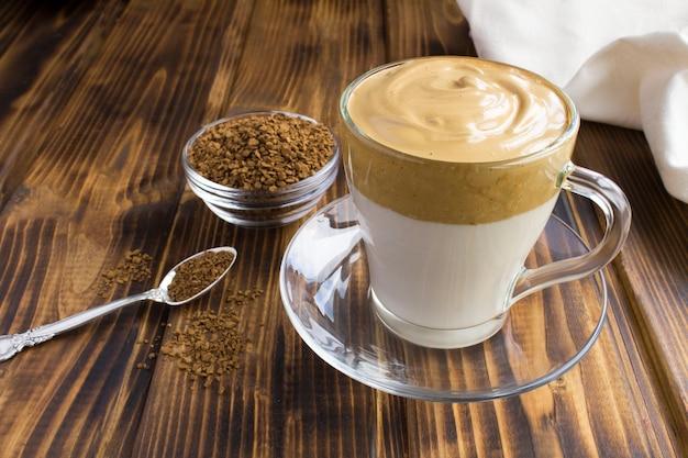 茶色の木製の背景のガラスのコップでダルゴナコーヒー。閉じる。