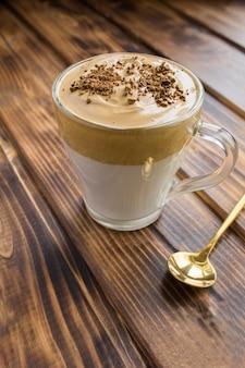 茶色の木製の背景のガラスのコップでダルゴナコーヒー。垂直方向の場所。