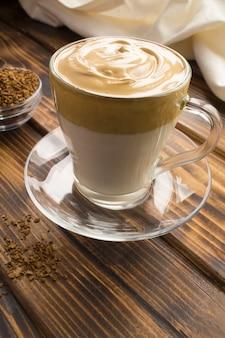 茶色の木の表面のガラスカップでダルゴナコーヒー。垂直方向の場所。