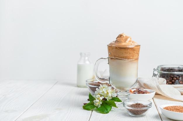 Кофе dalgona, ингредиенты и цветы на белой стене с пространством для копирования. вид сбоку, горизонтальный.