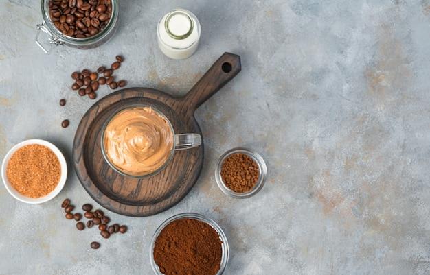 ダルゴナ コーヒーは韓国の飲み物で、泡立てたコーヒー フォーム、牛乳、お好みで氷を加えます。上面図。スペースをコピーします。
