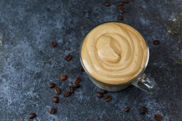 복사 공간 어두운 배경 평면도에 dalgona 커피. 거품 커피는 휘핑 인스턴트 커피, 설탕 및 우유와 함께 한국 유행 음료입니다.