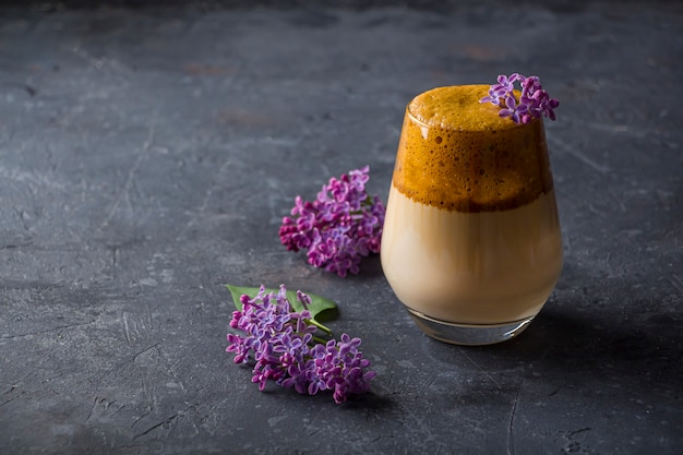 Dalgona coffee in tall glass with lilac flowers on dark background. instant coffee whipped with sugar and water and added to cold milk. cool summer drink.
