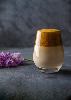 Dalgona coffee in tall glass with lilac flowers on dark. instant coffee whipped with sugar and water and added to cold milk. cool summer drink.