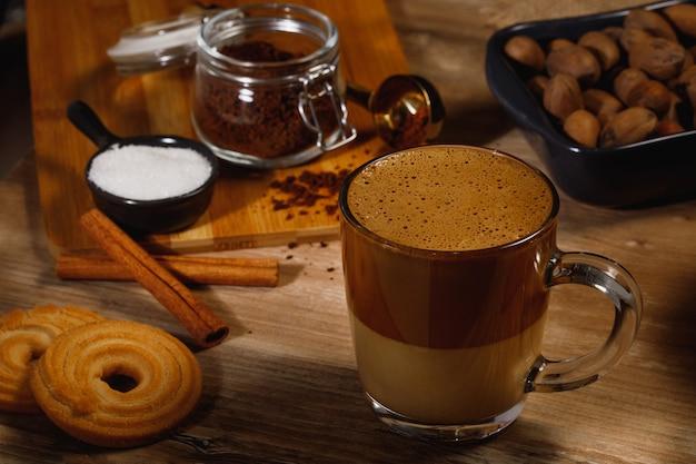 Dalgona coffee - корейский кофейный напиток на деревянном фоне. растворимый кофе или эспрессо, взбитые с сахаром и горячей водой. замороженная взбитая концепция кофе далгона. взгляд сверху.