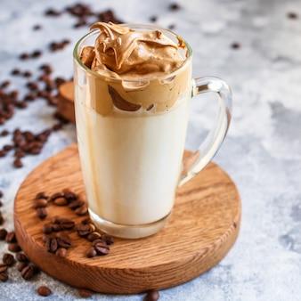 Dalgona 커피 트렌드 아이스 음료 카푸치노 또는 라떼 무성한 크림 휘핑 메뉴 개념 건강 한 식습관입니다. 음식 배경 상위 뷰 텍스트 복사 공간