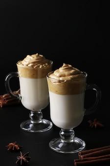 Дальгона сливочный кофе в два стакана на черной поверхности со взбитой пеной. корейский кофейный тренд, вертикальный формат