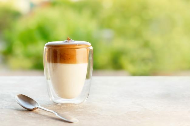 緑の背景のテーブルにスプーンでガラスのダルゴナ泡状コーヒー。テキストのコピースペースを持つインスタントコーヒーの泡とトレンド韓国アイスラテコーヒードリンク。