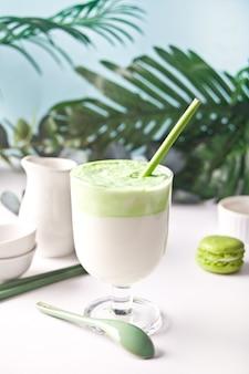 Dalgona matcha latte,creamy whipped matcha green tea with plant on the background.
