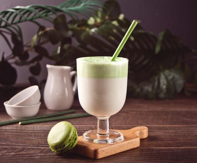 Dalgona matcha latte, сливочный взбитый зеленый чай матча с растениями на заднем плане.