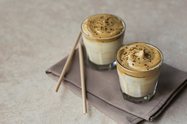 달고나 휘핑 커피, 인스턴트, 크림, 아이스 커피. 라이트 베이지에 커피, 우유, 얼음 조각이있는 칵테일