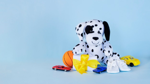 Dalmatian puppy toy with small present toy cars and basketball ball on light blue background