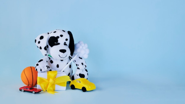 Dalmatian puppy toy with small present and toy cars on light blue background
