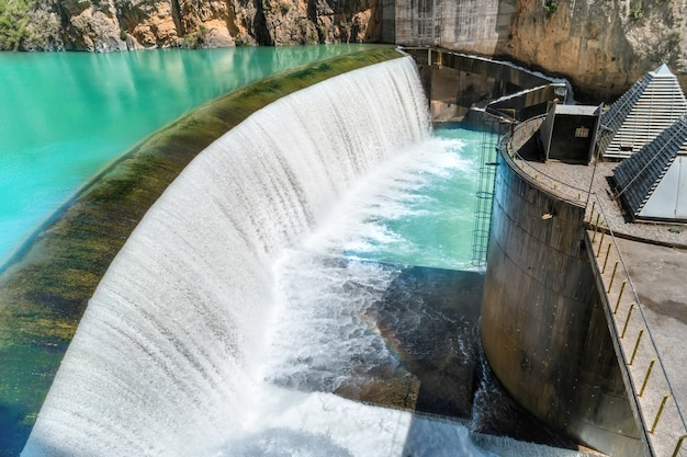 Плотина на реке сегре с голубой водой в горах. каскад с водопадом