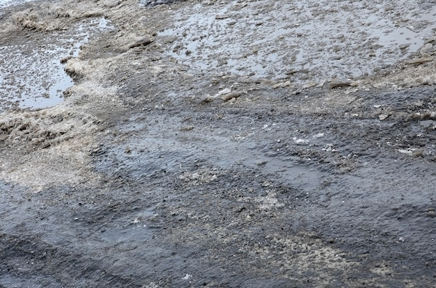 Damaged asphalt road with potholes caused by freezing