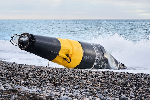 Поврежденный черно-желтый морской буй (знак кардинальной опасности), выброшенный на берег после шторма