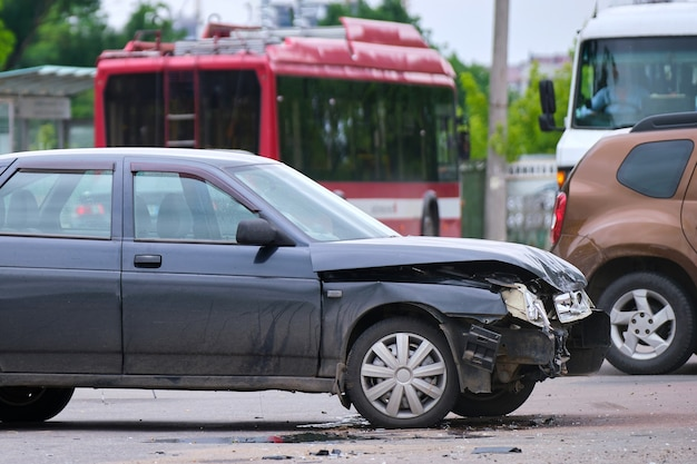 Damaged in car accident vehicle on city street crash site.
