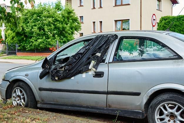 Поврежденный автомобиль припаркован на городской дороге