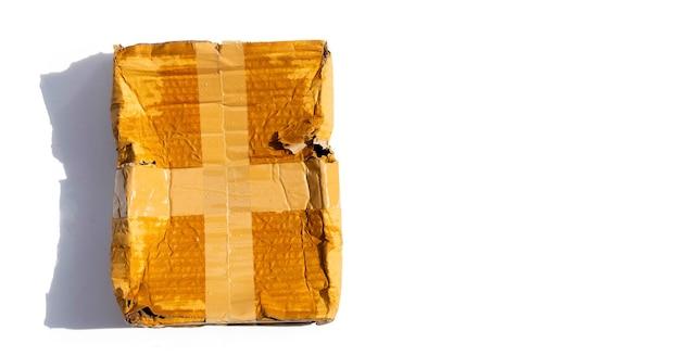 Поврежденная картонная коробка с отверстием, сломанная и влажная упаковка продукта