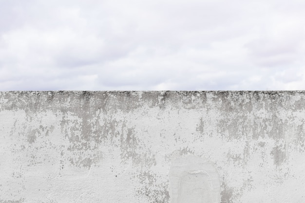 Damaged cement wall background and clowdy sky