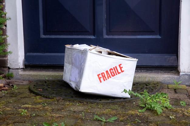 家の正面玄関にある破損した配達用段ボール箱へこみのある壊れやすいパッケージ配達不良