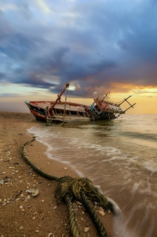 The damaged fishing boat is located on a coast in pattaya, thailand.