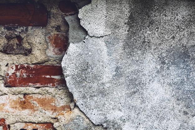 Damaged grey wall with red bricks peeking through.