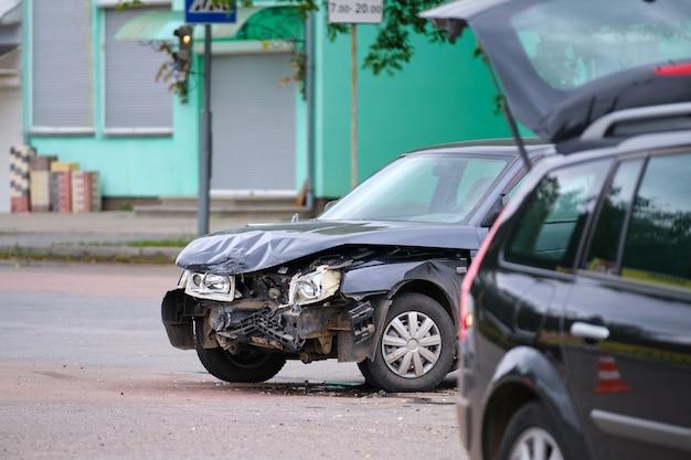 Поврежденный в автокатастрофе автомобиль на месте аварии на городской улице.