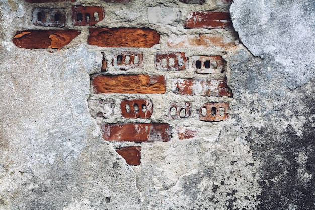 Damaged old wall with bricks red showing through.