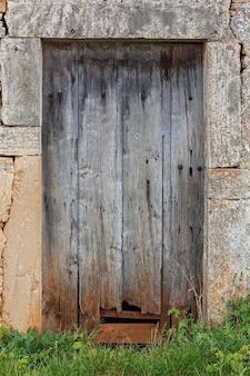 草が生い茂った損傷した古い木製のドア