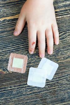 子供の手の1本の指が損傷し、すでに治癒して治療されている損傷のある手のクローズアップ、石膏が傷に適用されます