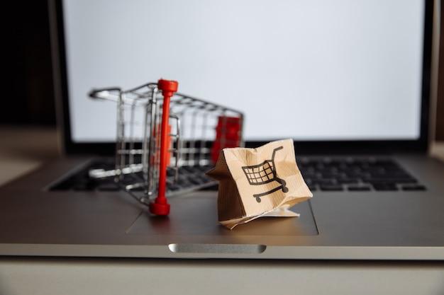Поврежденная бумажная коробка и тележка для покупок на клавиатуре ноутбука. концепция доставки. отгрузка авария.